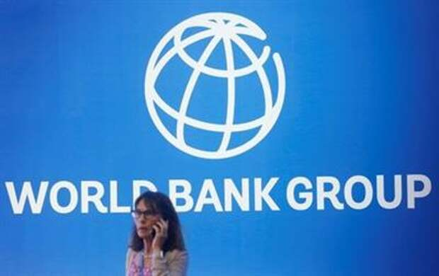 FILE PHOTO: A participant stands near a logo of World Bank at the International Monetary Fund - World Bank Annual Meeting 2018 in Nusa Dua, Bali, Indonesia, October 12, 2018. REUTERS/Johannes P. Christo/File Photo