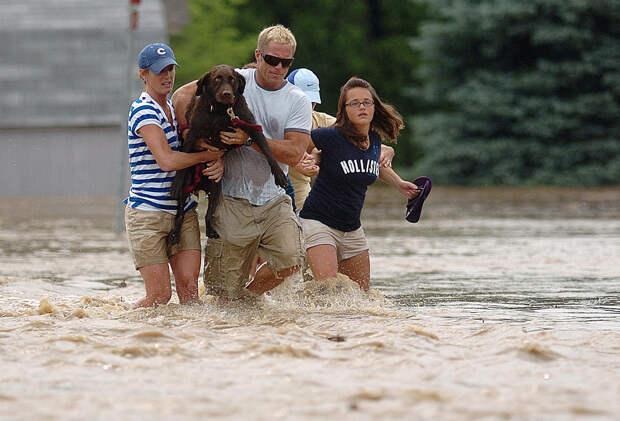 Местных жители идут в воде вдоль дороги Роки Форд в городе Колумбус, штат Индиана, чтобы добраться до незатопленных высот, 7 июня 2008. Сотни жителей были бы спасены, после того, как паводковые воды затопили несколько районов города. В результате наводнения погиб один человек и были нанесены убытки в размере нескольких миллионов. (AP Photo/The Columbus Republic, Mike Dickbernd)