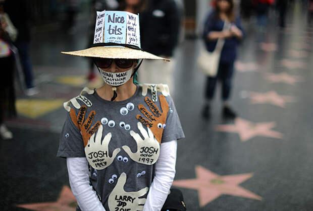Активистка во время марша протеста против сексуальных домогательств. На ее одежде имена всех людей, которые когда-то к ней домогались. Лос-Анджелес, США