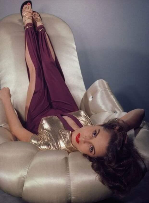 Позирует на камеру в превосходном наряде бордового цвета с разрезами.