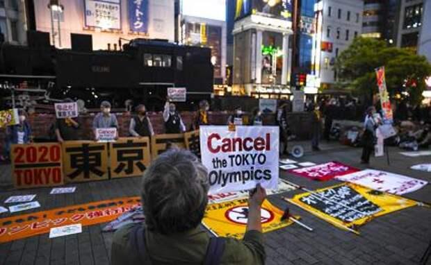 На фото: протестующий держит плакат с требованием отмены Олимпийских игр в Токио. Около 30-40 протестующих вышли на улицы, их сопровождало столько же сотрудников милиции