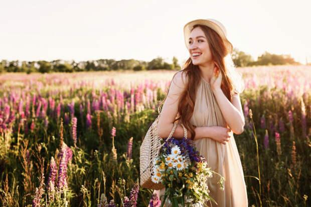 Счастливый молодая девушка, ходить в поле цветов на закате ...