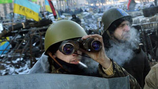 Протестующий на Площади Независимости смотрит в бинокль на заблокированный участок дороги