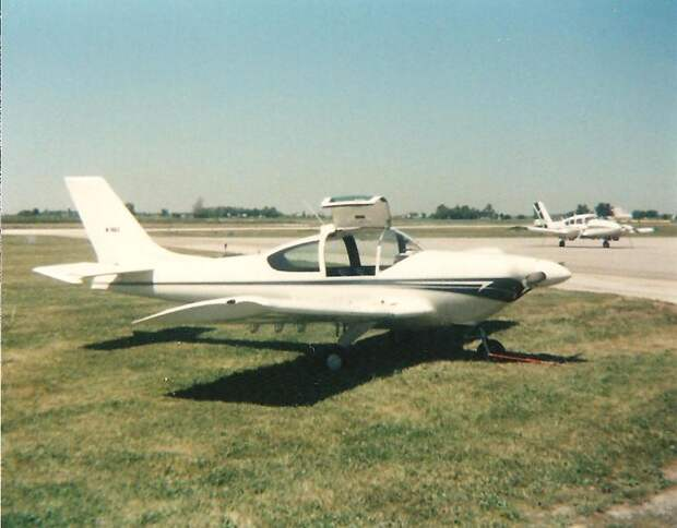 A low winged single-engined aircraft parked