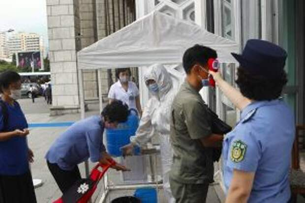 На фото: измерение температуры тела у пассажиров на центральной железнодорожной станции в Пхеньяне во время пандемии коронавируса COVID-19