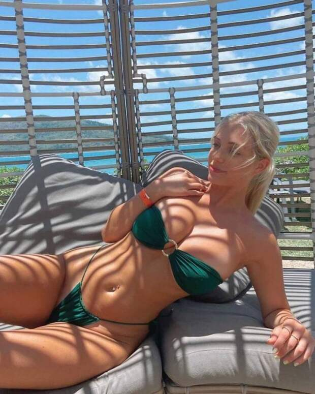 Девушка в зеленом раздельном купальнике загорает