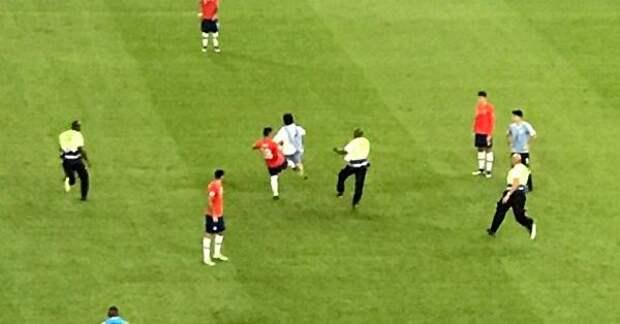 Футболист сборной Чили ударил фаната, выбежавшего наполе вмаске петуха