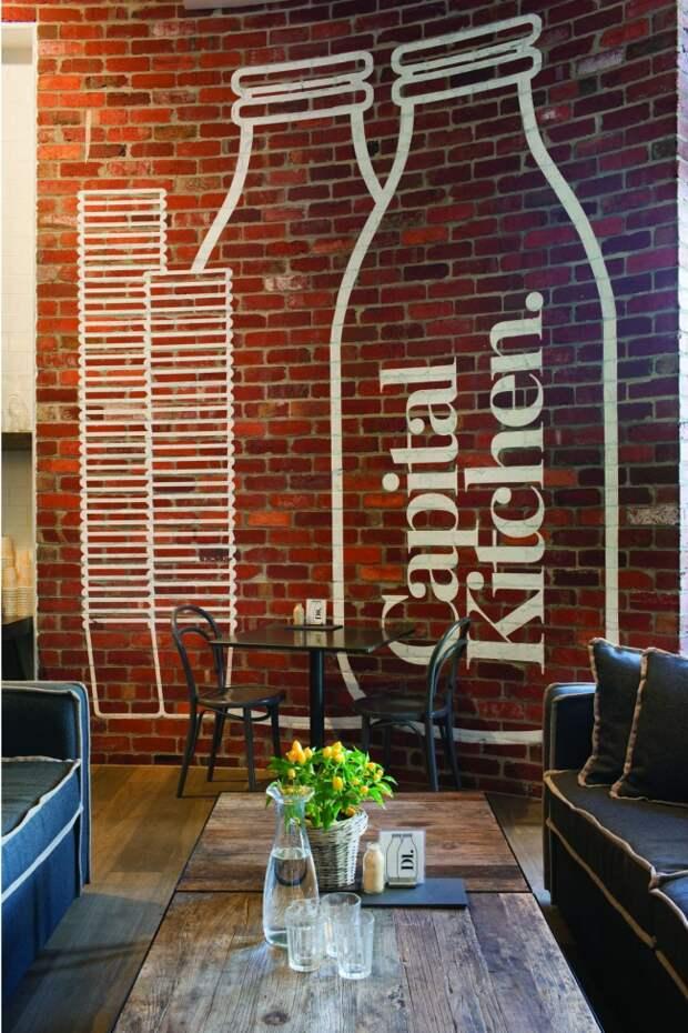 Очень атмосферное лофтовое помещение с кирпичной кладкой на всю стену и большим графическим рисунком белого цвета