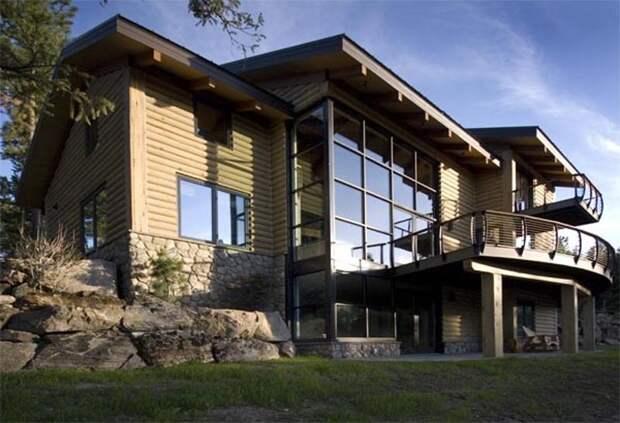 Огромный деревянный дом, с полностью застекленной гостиной и большой террасой.