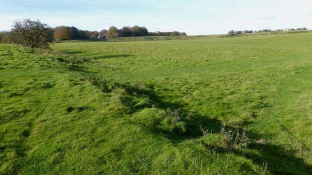 На переднем плане - южная стена Даррингтонских стен доисторического места недалеко от Даррингтона в Уилтшире. На заднем плане изображения - западная стена участка.