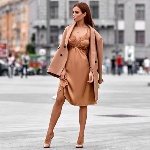 девушка в бежевом платье и плаще на улице