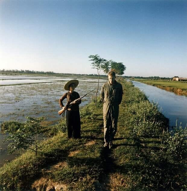 Пойманный в плен американский майор Дьюи Уодделл охраняется милиционеркой с оружием и штыком на рисовом поле. Вьетнам, 1967 .  история, люди, фото