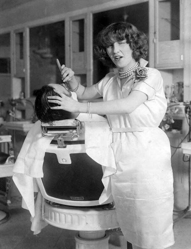 Первая лицензированная женщина парикмахер Нью-Йорка мисс Джин Деверо позирует фотографу во время бритья клиента, 1927 год  история, люди, фото