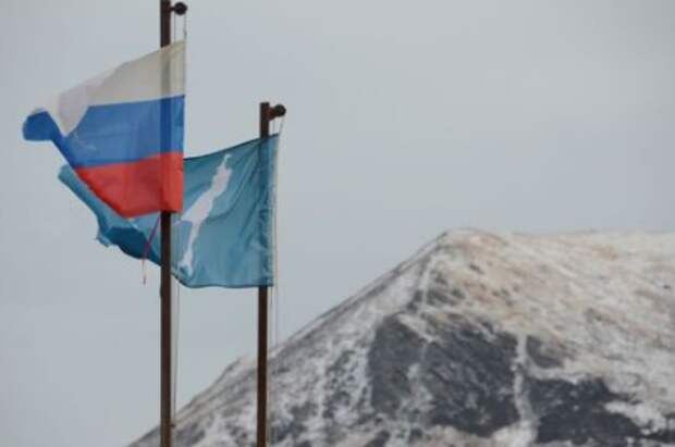 A national flag of Russia and a flag of Russia's Sakhalin region flutter in the village of Malokurilskoye on the island of Shikotan, Southern Kuriles, Russia, December 18, 2016. REUTERS/Yuri Maltsev